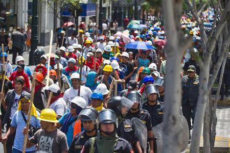 Mineros informales en una protesta en el centro de Lima son escoltados por policías de choque, el 25 de marzo de 2014 AFP / ERNESTO BENAVIDES